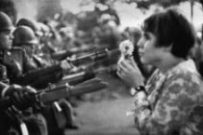 a woman holds a flower in front of armed men