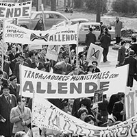 a crowd of people holding signs in support of Allende