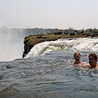 An image of two people swimming on the edge of a waterfall