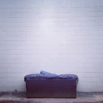 a white brick wall with a couch in front of it